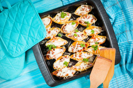 Italian pasta Conchiglioni Rigati stuffed with cheese and meat on blue wood table. Stock Photo