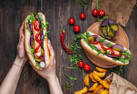 Hot dog in the hands of women on a wooden table. Top view Stok Fotoğraf