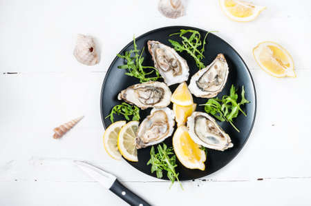 Oysters with lemon fruit on a black plate on a white wood table. Top view