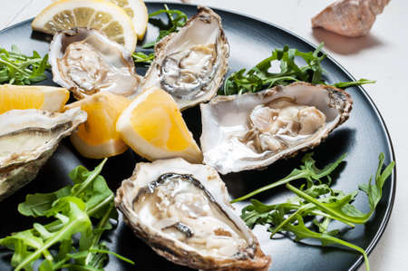 Oysters with lemon fruit on a black plate on a white wood table
