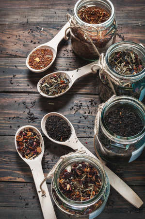 loose leaf: Different kinds of tea in jar and wooden spoons on wood table.