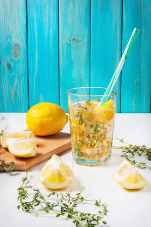 lemonade with mint and on rocks served in jar with a straw on a wooden table. Copyspace Stok Fotoğraf