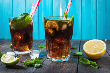 longdrink: Homemade Cuba Libre with fresh lime, brown rum and crushed ice on an old wooden table.