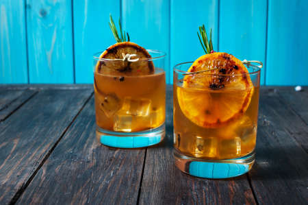 Alcohol cocktail with lemon, ice and smoking rosemary on dark table. Stock Photo