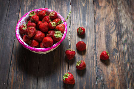 fresh strawberries in a basket on wood background.