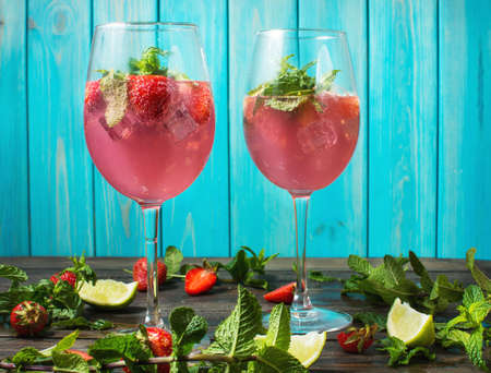daiquiri alcohol: Strawberry cocktails with lime and ice cubes on rustic background.