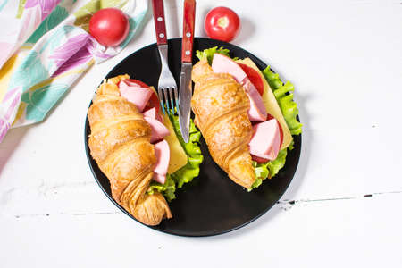 Light and hearty spring breakfast. Croissant with ham, cheese, fresh tomatoes on a white stone table. Stock Photo