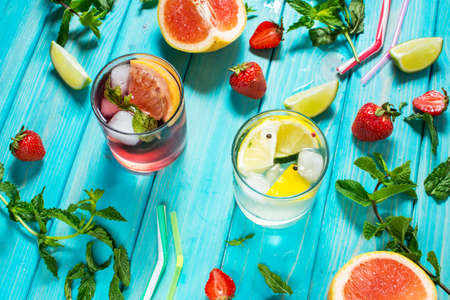 Glass of alcohol cold coctail decorated with ice, fruit and mint staying on wood table. Fresh juice on background with lemon, strawberry, lime