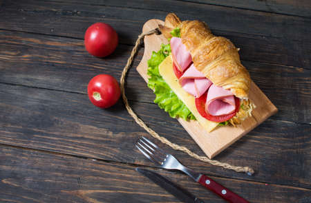 Light and hearty spring breakfast. Croissant with ham, cheese, fresh tomatoes on a wood stone table Фото со стока