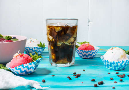 Iced coffee in glass and ice cream on blue wood background Stock Photo