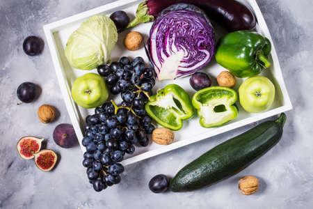 Fresh organic raw green and purple colored vegetables and fruits in white tray on dark stone background.