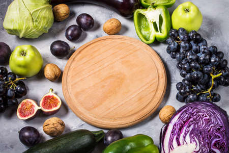 Fresh organic raw green and purple colored vegetables and fruits on stone background. Copyspace