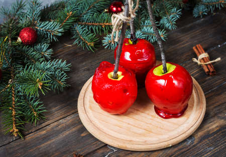 Red caramel apples on sticks on Dark wood background, with Christmas tree branches