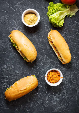 Hot dog with pickles and lettuce on concrete background.