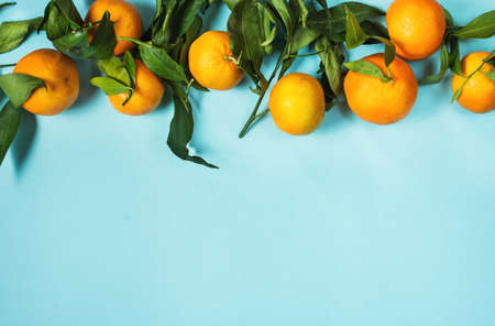 Fresh mandarin with leaves isolated on blue background. Flat lay. Top view