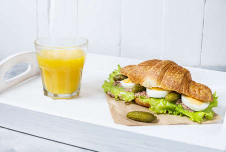 Croissant sandwich with tuna, hard boiled egg, salad and cucumber on white tray. Glass of orange juice. Breakfast