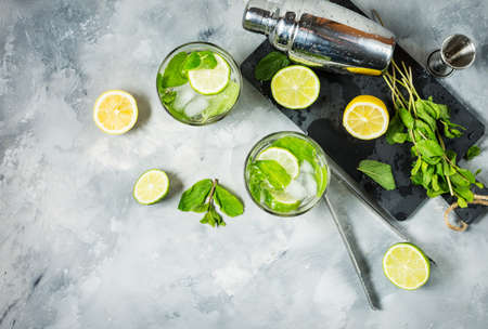 Mojito cocktail with lime and mint in highball glass on a stone table. Drink making tools and ingredients for cocktail. Top view