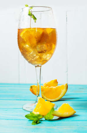 Negroni cocktail with an orange on blue wood table.
