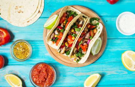 Mexican pork tacos with vegetables. Tacos al pastor on wooden blue rustic background.