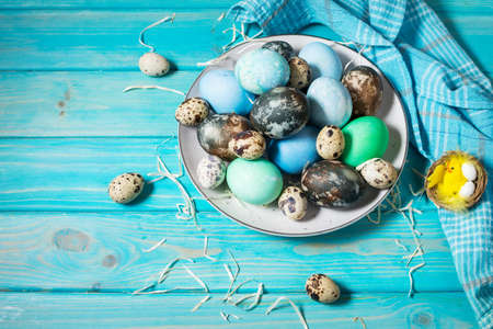 painted eggs on plate, quail and chicken eggs, paint and brush on blue wood background, Easter decorations. Stock Photo