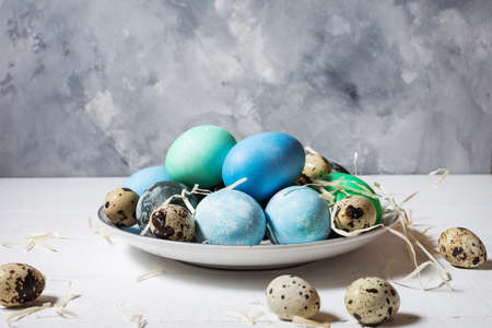 painted eggs on plate, quail and chicken eggs, paint and brush on white wood background, Easter decorations.