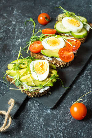 Tasty sandwiches with egg, avocado and vegetables on stone black background. Stock Photo