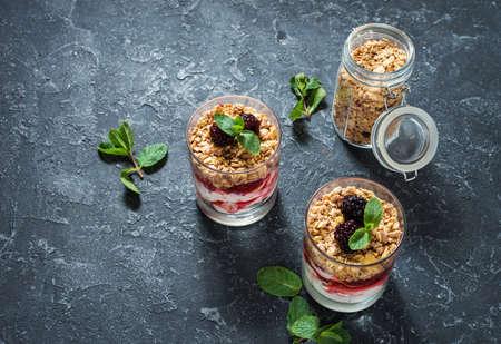 Healthy layered dessert with yogurt, granola, jam, blackberry in glass on stone background.