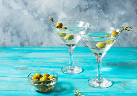 Martini cocktail with green olives on blue wood background.