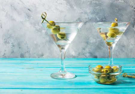 Cóctel de Martini con aceitunas verdes sobre fondo de madera azul.