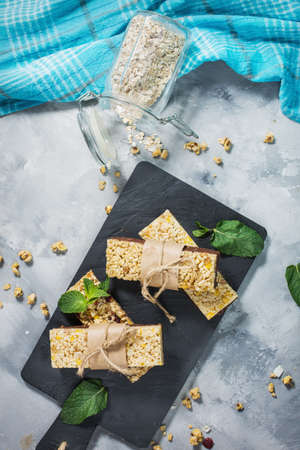 Granola energy bars with oatmeal, almond, dry cranberry. Healthy snack on concrete background. Фото со стока