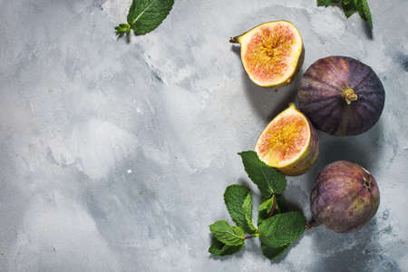 Ripe sweet figs with green leaves on concrete background. Top view and copy space Banque d'images