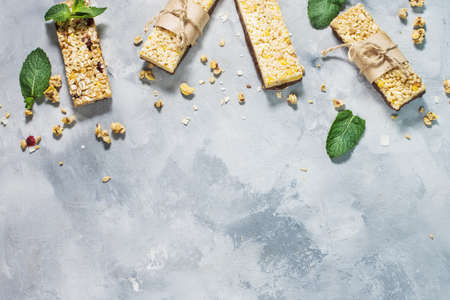 Granola energy bars with oatmeal, almond, dry cranberry. Healthy snack on concrete background