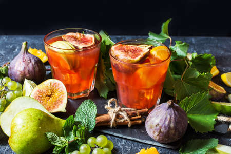 Cocktail fruit sangria with apples, orange, figs, grapes on stone table
