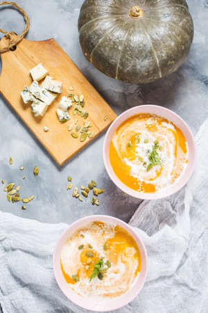 Thick pumpkin soup with feta cheese on concrete background. Top view