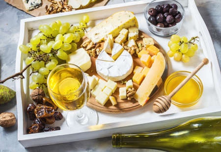 Different types of cheese on wooden board, olive, fruits, almond and wine glasses on white tray on concrete table Reklamní fotografie