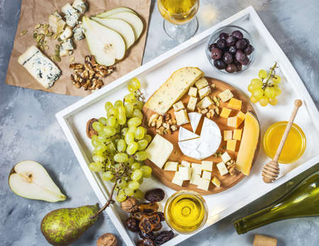 Different types of cheese on wooden board, olive, fruits, almond and wine glasses on white tray. Top view Фото со стока