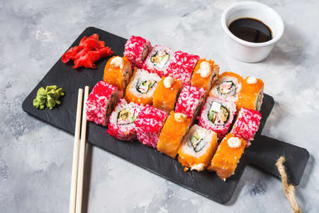 Assorted sushi rolls set served on plate on concrete background.