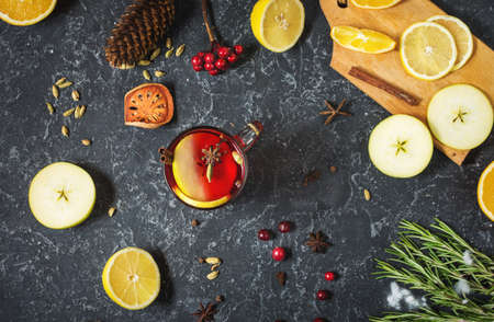 Christmas mulled wine with spices and orange slices on stone table. Traditional drink on winter holiday.