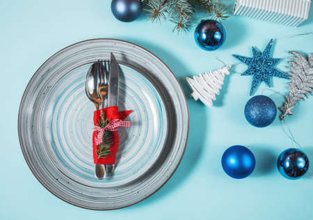 Christmas table place setting on blue background. Top view