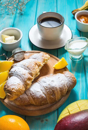 Breakfast served with coffee, orange juice, croissants and fruits on blue background