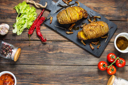 Roasted hasselback potato on wooden background. Top view and copy space Stock fotó