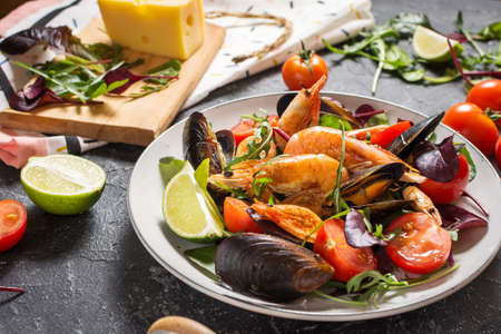 Fresh seafood salad, mussels, shrimp, fresh vegetables and herbs on black stone background