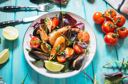 Fresh seafood salad, mussels, shrimp, fresh vegetables and herbs on blue wooden table.