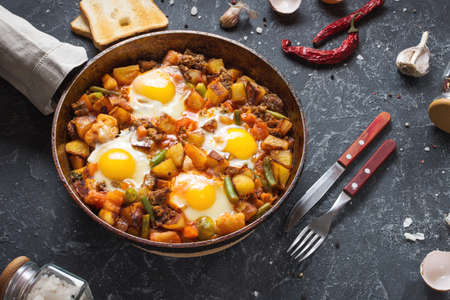 Homemade Hearty Breakfast Skillet with Eggs Potatoes and minced meat on stone table