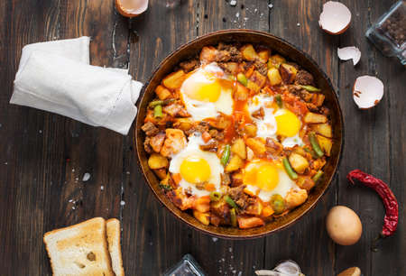 Homemade Hearty Breakfast Skillet with Eggs Potatoes and minced meat on wooden table 免版税图像