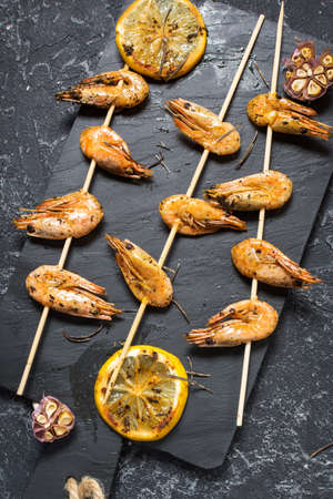Grilled shrimp skewers with herbs, garlic and lemon on black stone background. Seafood, shelfish.