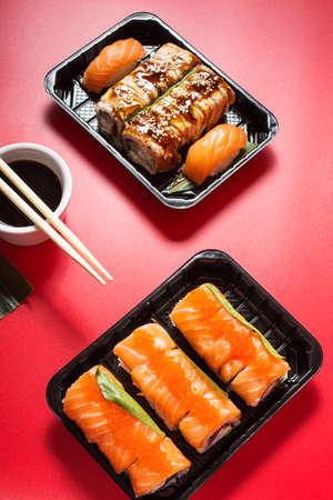 Various kinds of sushi served on red background