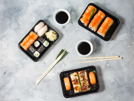 Various kinds of sushi served on concrete background.