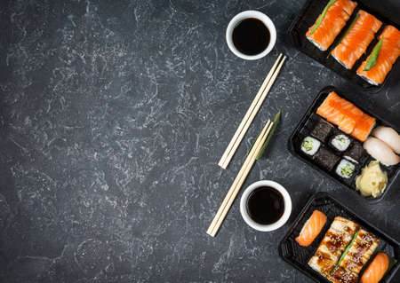 Various kinds of sushi served on black stone background. Top view and copy space