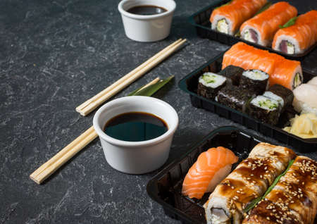 Various kinds of sushi served on black stone background.